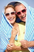 Senior Couple Sheltering From Sun On Beach Holiday — Stock Photo