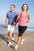 Senior Couple Exercising On Beach — Foto de Stock