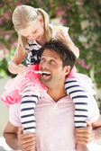 Ojciec daje córka jazdy na ramionach, podczas karmienia lodu cr — Zdjęcie stockowe
