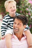 Father Giving Son Ride On Shoulders Outdoors — Stock Photo