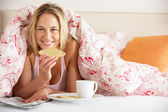 Pretty Woman Snuggled Under Duvet Eating Breakfast And Reading N — Stock Photo