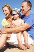 Grandparents And Grandson Sitting On Beach — Stock Photo
