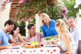 Group Of Young And Senior Couples Enjoying Family Meal — Stock Photo