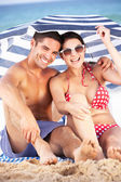 Couple Sheltering From Sun Under Beach Umbrella — Stock Photo