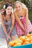 Two Women Pushing Wheelbarrow Filled With Oranges — Stock Photo