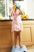 Ragazza in piedi sul gradino plastica in cucina aiutando con detersivo — Foto Stock