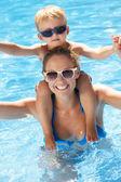 Madre e hijo se divierten en la piscina — Foto de Stock
