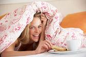 Pretty Woman Snuggled Under Duvet Eating Breakfast — Stock Photo