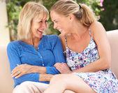 Starszy kobieta z córka dorosły relaksujący na kanapie w domu — Zdjęcie stockowe