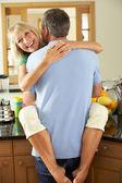Romantica coppia senior abbracciarsi in cucina — Foto Stock