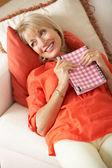 Senior donna seduta sul divano leggendo il diario — Foto Stock