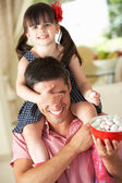 Father Giving Daughter Ride On Shoulders Indoors Whilst Eating M — Stock Photo