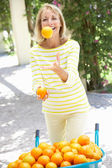 Senior Woman Juggling Oranges By Wheelbarrow — Stock Photo