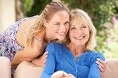 Senior Woman With Adult Daughter Relaxing On Sofa At Home — ストック写真