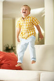 Young Boy Jumping On Sofa At Home — Stok fotoğraf