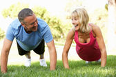 Senior Couple Exercising In Park — 图库照片