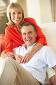 Senior Couple Relaxing On Sofa At Home — Stock Photo