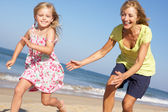 Grandmother And Granddaughter Running Along Beach — Stock Photo