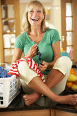 Senior Woman Sorting Laundry In Kitchen — Stock Photo