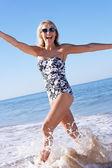 Starší žena požívající dovolenou na pláži — Stock fotografie