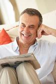 Uomo anziano lettura giornale di relax sul divano di casa — Foto Stock