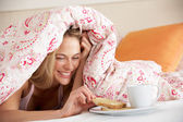 Pretty Woman Snuggled Under Duvet Eating Breakfast — Stock Photo