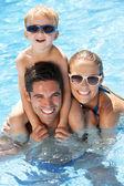Familia divirtiéndose en la piscina — Foto de Stock