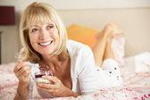 Senior Woman Eating Dessert In Bed — Stock Photo