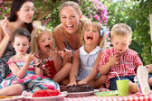 Children And Mothers Eating Jelly And Cake At Outdoor Tea Party — Foto Stock