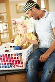 Padre e figlio l'ordinamento lavanderia seduta sul bancone della cucina — Foto Stock