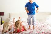 Kinder springen auf dem bett — Stockfoto
