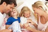Familia relajante juntos en la cama — Foto de Stock
