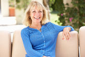 Senior Woman Relaxing On Sofa At Home — Stock Photo