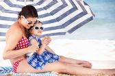 Madre e figlia sotto ombrellone mettendo sulla crema solare — Foto Stock