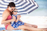 Mother And Daughter Under Beach Umbrella Putting On Sun Cream — Foto Stock