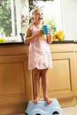 キッチン食器洗いを手伝ってのプラスチック製のステップに立っている女の子 — ストック写真