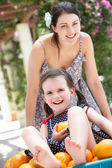 Mother Pushing Daughter In Wheelbarrow Filled With Oranges — Stock Photo