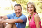 Senior Couple Resting After Exercising In Park — Foto Stock