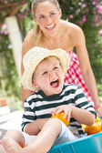 Mother Pushing Son In Wheelbarrow Filled With Oranges — Stock Photo