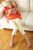 Senior Woman Sitting On Sofa Reading Diary — Stock Photo