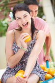 Man Pushing Woman In Wheelbarrow Filled With Oranges — Stock Photo