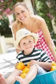 Madre, spingendo il figlio in una carriola piena di arance — Foto Stock