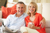 Senior Couple Relaxing On Sofa At Home Reading Newspaper — Stock Photo