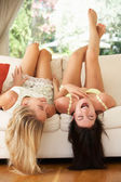 Two Female Friends Lying Upside Down On Sofa — Stock Photo