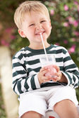 Giovane ragazzo indossa wellington stivali bere milkshake — Foto Stock