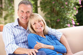 Senior Couple Relaxing On Sofa At Home — Stock fotografie