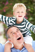 Grandfather Giving Grandson Ride On Shoulders Outdoors — Stock Photo
