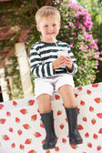 Young Boy Wearing Wellington Boots Drinking Milkshake — Stock Photo