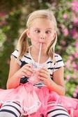 Junges mädchen mit rosa wellington stiefel trinken milchshake — Stockfoto