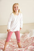Young Girl Bouncing On Bed — Stock Photo